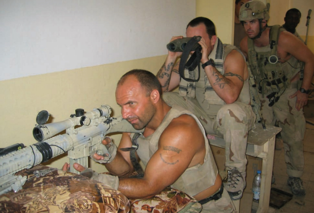 SSgt Chadwick D. Baker mans a suppressed SR-25 7.62mm sniper rifle during the battle of an-Najaf in August 2004. Spotting for him is HM1 Matthew S. Pranka, and behind Pranka is SSgt Jack A. Kelly. Watching from the door are Sgts Miguel