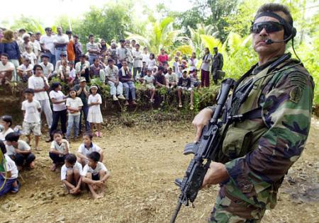 Lunedi 29 luglio 2002, isola di Basilan, Repubblica delle Filippine: un Green Beret, armato di un CAR M4 S.O.P.MOD. (Special Operation Peculiar Modification), vigila su di un nutrito gruppo di civili presenti all' inaugurazione di un ponte nel villaggio di Maluso, nell' area sud dell' isola di Basilan. Il ponte in questione è stato edificato grazie agli sforzi del governo britannico (foto © Associated Press / Aaron Favila)